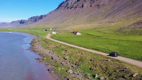 Aerial-over-a-black-van-traveling-on-a-dirt-road-in-Iceland-near-Raudisandur-Beach-in-the-Northwest-Fjords-5