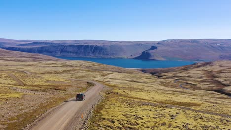 Aerial-over-a-black-camper-van-traveling-on-a-dirt-road-in-Iceland-in-the-Northwest-Fjords