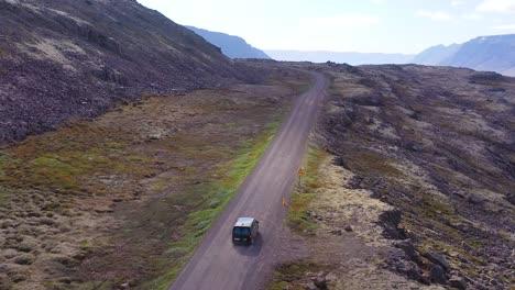 Steigende-Antenne-über-Einem-Schwarzen-Wohnmobil-Das-Auf-Einer-Unbefestigten-Straße-In-Island-In-Den-Nordwestlichen-Fjorden-Reist
