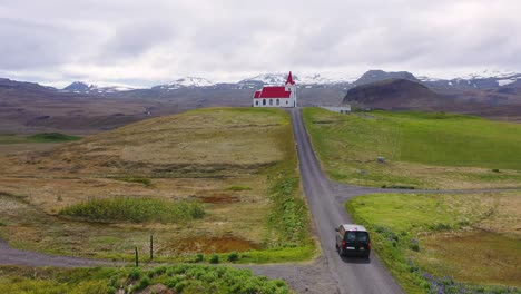 Aerial-over-a-black-camper-van-driving-up-to-a-church-on-a-hill-in-the-mountains-of-Iceland-2