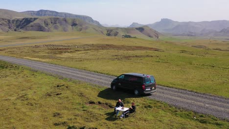 Aerial-over-two-men-enjoying-a-picnic-beside-a-black-camper-van-in-the-mountains-of-Iceland