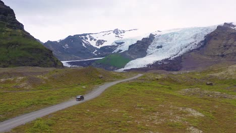Aerial-over-a-black-camper-van-driving-up-to-a-remote-glacier-in-the-mountains-of-Iceland