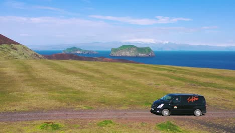 Aerial-over-a-black-camper-van-traveling-on-a-dirt-road-in-Iceland-in-the-Westmann-islands