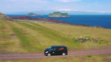 Aerial-over-a-black-camper-van-traveling-on-a-dirt-road-in-Iceland-in-the-Westmann-islands-1