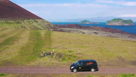 Aerial-over-a-black-camper-van-traveling-on-a-dirt-road-in-Iceland-in-the-Westmann-islands-2