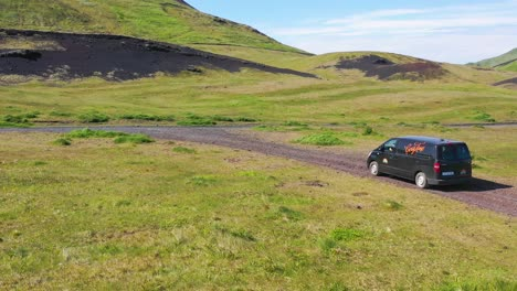 Aerial-over-a-black-camper-van-traveling-on-a-dirt-road-in-Iceland-in-the-Westmann-islands-3