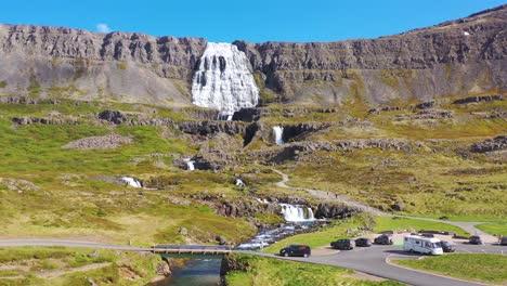 Beautiful-aerial-shot-of-camper-van-driving-on-road-Dynjandi-waterfall-in-the-Westfjords-of-Iceland