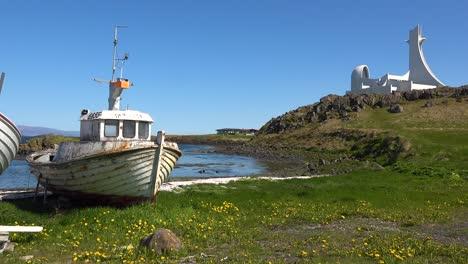 An-abandoned-landlocked-fishing-boat-with-modernist-architecture-of-Stykkish_____'lmskirkja-church-Iceland