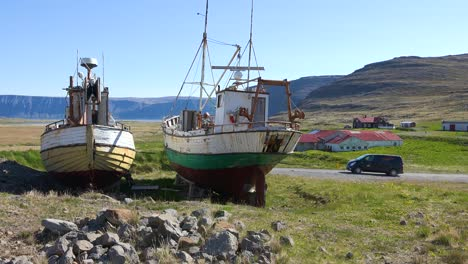 A-camper-van-drives-past-landlocked-fishing-boats-in-the-remote-Westfjords-of-Iceland