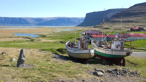 Abandoned-fishing-boats-sit-on-the-land-in-a-remote-fjord-in-Iceland-as-the-cod-industry-declines