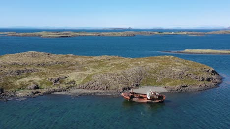 Aerial-over-abandoned-fishing-boat-sitting-on-the-shore-of-the-Westfjords-Iceland-1