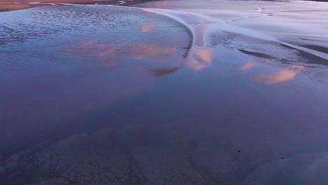 Toma-Aérea-De-Reflejos-De-Nubes-En-La-Bahía-De-Mareas-Y-Patrones-De-Atardecer-Cerca-De-La-Playa-De-Rau______isandur-Westfjords-Islandia
