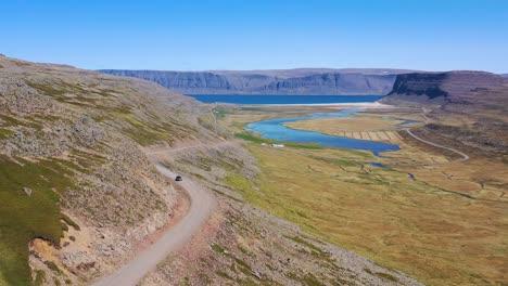 Schöne-Luftaufnahme-Eines-Autos-Das-Auf-Einer-Unbefestigten-Straße-Mit-Den-Westfjorden-Und-Fjorden-Islands-Fährt