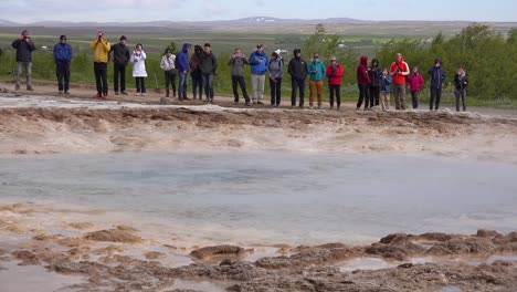 Strokkur-geyser-erupts-in-front-of-tourists-in-Iceland