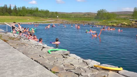 Tourists-and-Icelanders-enjoy-a-bath-in-a-hot-water-geothermal-spring-in-iceland-at-Fludir-Secret-Lagoon-1