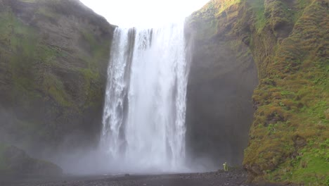 A-man-walks-close-to-the-Skogafoss-waterfall-in-Iceland
