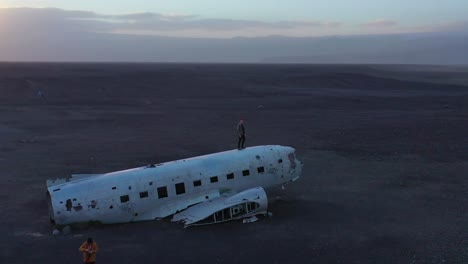 Aerial-man-standing-on-a-crashed-US-Navy-DC-3-on-the-black-sands-of-Solheimasandur-Iceland-1