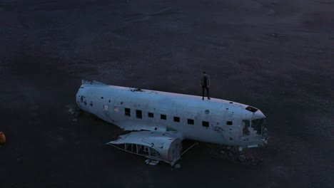 Aerial-man-standing-on-a-crashed-US-Navy-DC-3-on-the-black-sands-of-Solheimasandur-Iceland-2