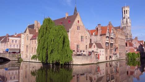 Pan-across-beautiful-canal-and-the-Belfort-Van-Brugge-Bruges-belfry-bell-tower-in-Belgium