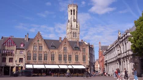 Establishing-shot-of-central-Bruges-Belgium-with-Belfort-Van-Brugge-belfry-bell-tower-and-bicycles-and-pedestrians-passing