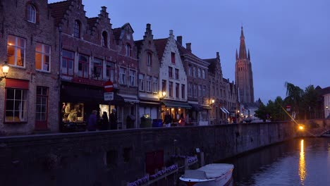 Street-of-shops-and-canal-at-night-in-Bruges-Belgium