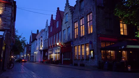 Street-of-shops-restaurants-and-canal-at-night-in-Bruges-Belgium