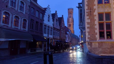Street-of-shops-restaurants-and-horse-cart-at-night-in-Bruges-Belgium