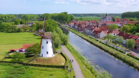 Aerial-over-canal-and-small-town-of-Damme-Belgium-and-historic-windmill-1