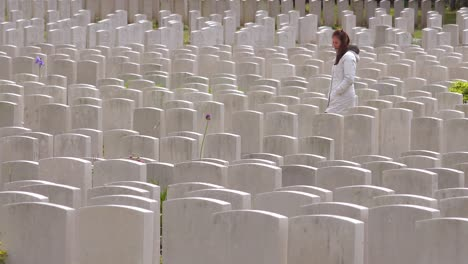 A-woman-in-a-white-coat-looks-at-headstones-of-the-Etaples-France-World-War-cemetery-military-graveyard-2