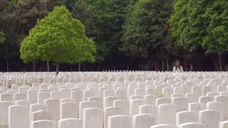 Una-Mujer-Fantasma-Con-Una-Bata-Blanca-Mira-Las-Lápidas-Del-Cementerio-De-La-Guerra-Mundial-De-Etaples-Francia-Cementerio-Militar-Luego-Se-Disuelve-Lentamente-Y-Desaparece
