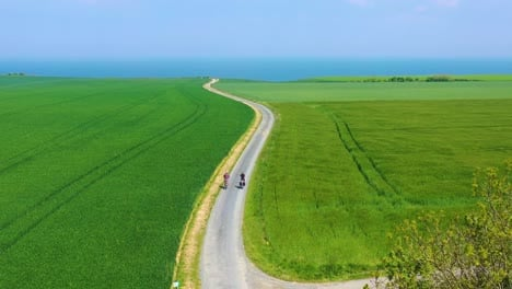 Beautiful-aerial-of-a-French-couple-riding-bicycles-through-the-green-countrside-of-Normandy-France-2