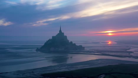 Moody-aerial-of-Mont-Saint-Michel-France-silhouetted-at-sunrise-in-fog