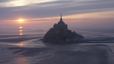 Moody-aerial-of-Mont-Saint-Michel-France-silhouetted-at-sunrise-in-fog-3