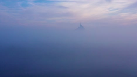 Moody-amazing-aerial-of-Mont-Saint-Michel-France-rising-out-of-the-mist-and-fog-in-early-morning