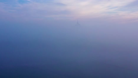 Moody-amazing-aerial-of-Mont-Saint-Michel-France-rising-out-of-the-mist-and-fog-in-early-morning-1