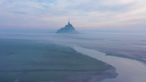 Moody-amazing-aerial-of-Mont-Saint-Michel-France-rising-out-of-the-mist-and-fog-in-early-morning-3