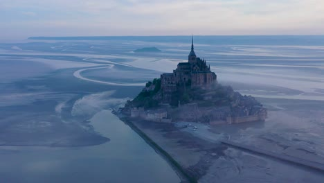 Foggy-aerial-of-Mont-Saint-Michel-France-in-the-mist-and-fog-in-early-morning