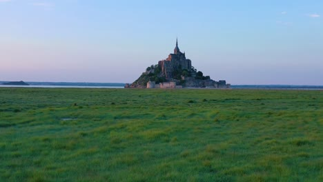Beautiful-daytime-rising-aerial-over-fields-of-grass-with-Mont-Saint-Michel-monastery-in-Normandy-France-background