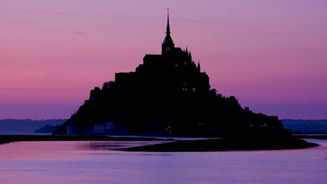 Mont-Saint-Michel-monastery-in-France-at-dusk-or-night-in-golden-purple-light