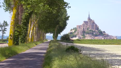 A-pretty-road-through-the-countryside-with-Mont-Saint-Michel-monastery-island-in-distance-Normandy-France