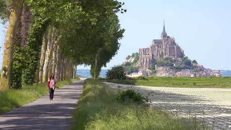 A-woman-walks-on-a-pretty-road-through-the-countryside-with-Mont-Saint-Michel-monastery-island-in-distance-Normandy-France
