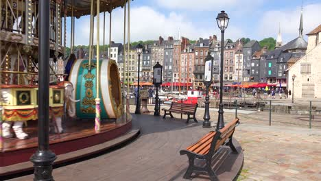 A-merry-go-round-turns-with-the-French-city-of-Honfleur-in-background