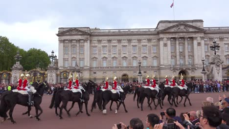 Buckingham-palace-mounted-guards-ride-horses-in-front-of-Buckingham-Palace-London-England