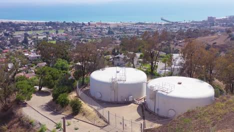Antena-Sobre-Tanques-De-Agua-En-Lo-Alto-De-Una-Colina-Sobre-La-Ciudad-De-Ventura-California