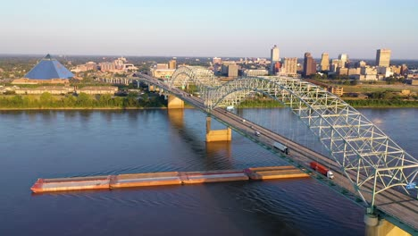 Good-aerial-over-the-Hernando-de-Soto-Bridge-Mississippi-River-and-barge-revealing-Memphis-Tennessee