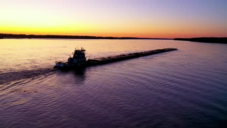 Very-good-aerial-of-a-tugboat-pushing-a-barge-up-the-Mississippi-River-near-Memphis-Tennessee-at-dusk