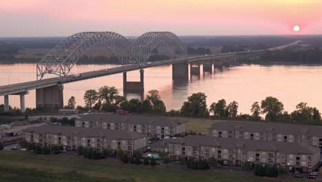 Sunset-behind-the-Hernando-de-Soto-Bridge-over-the-Mississippi-River-in-Memphis-Tennessee-with-apartment-complex-foreground