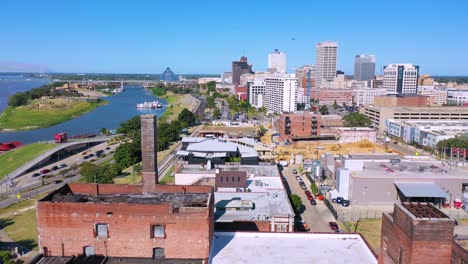 Aerial-over-Memphis-Tennessee-waterfront-and-Mud-Island-with-Memphis-pyramid-background-and-old-brick-factories-foreground