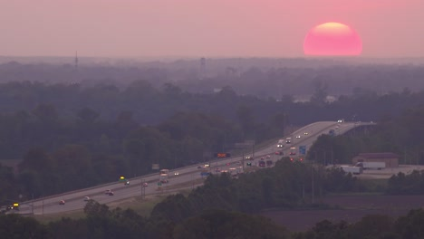 A-giant-ball-of-a-sunset-setting-sun-behind-busy-highway-or-freeway-traffic-near-Memphis-Tennessee