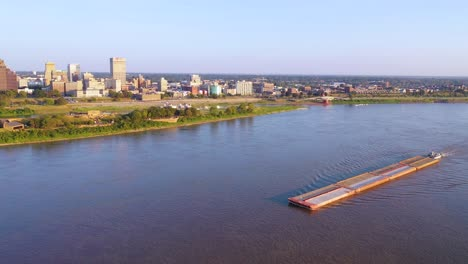 Good-aerial-over-a-barge-on-the-Mississippi-River-with-downtown-business-district-of-Memphis-Tennessee-in-background